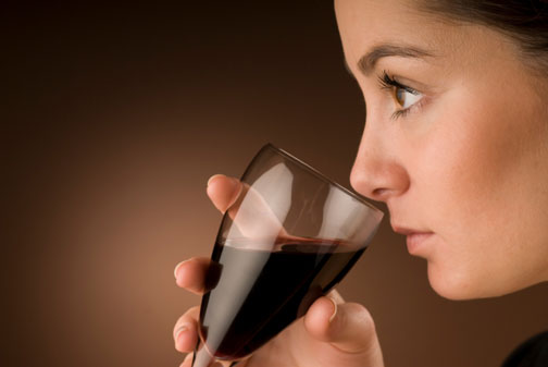 A beatiful young woman is tasting wine
